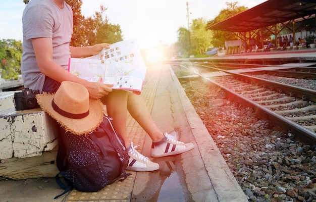 young man traveler with backpack and hat at the train station with a traveler , travel and recreation concept Free Photo