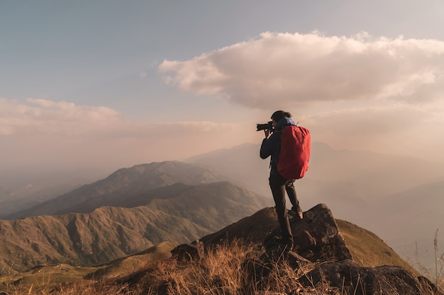 Young man traveler with backpack taking a photo on mountain Premium Photo