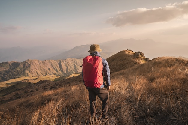 Young man traveler with backpack trekking on mountain, adventure travel lifestyle concept Premium Photo