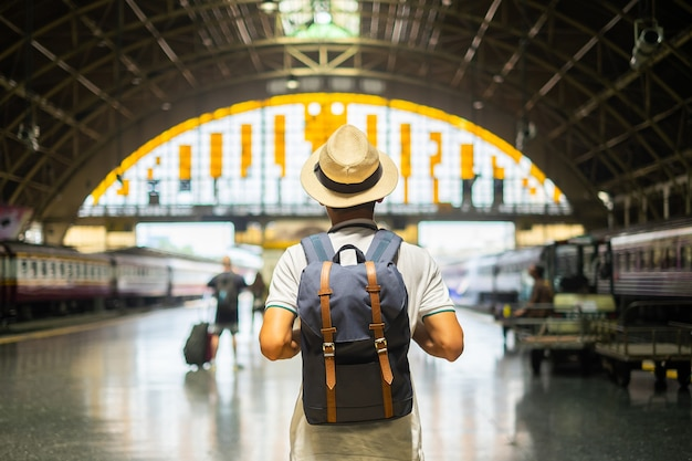 Young man traveler with backpack waiting for train Premium Photo