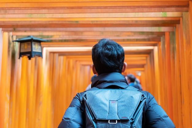 Молодой человек путешествуя на святыне fushimi inari taisha, счастливый азиатский путешественник смотря яркие оранжевые ворота torii. достопримечательности и популярные для туристов достопримечательности в киото, япония. концепция путешествия по азии Premium Фотографии