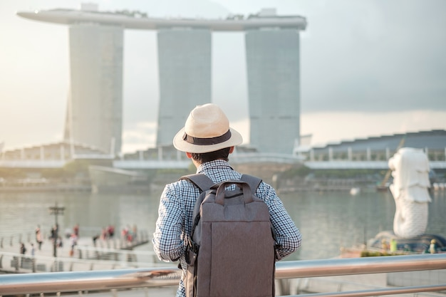 Young man traveling with backpack and hat in the morning, solo asian traveler visit in singapore city downtown. landmark and popular for tourist attractions. asia travel concept Premium Photo