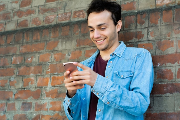 Young man typing on his phone Premium Photo