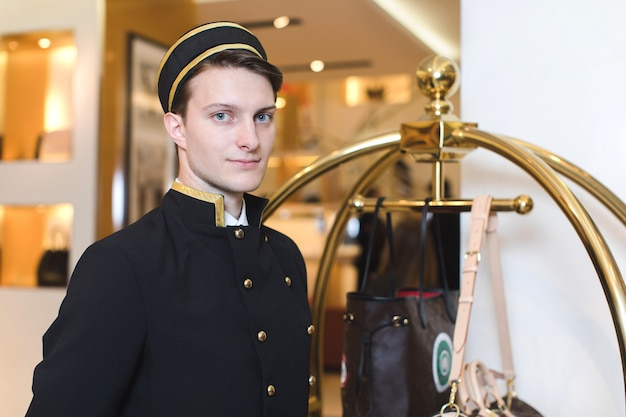 Young man in uniform serving in hotel Premium Photo