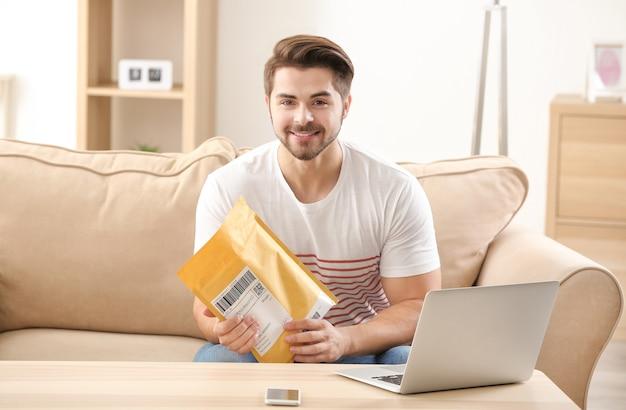 自宅で小包を開梱する若い男 Premium写真
