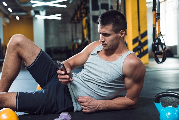 Young man using cellphone in gym Free Photo