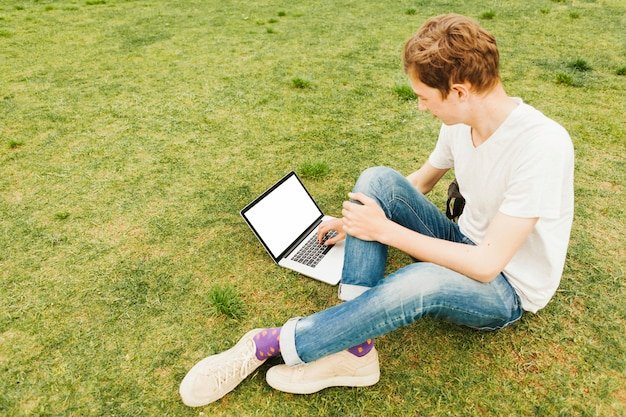 Young man using laptop on green grass Free Photo