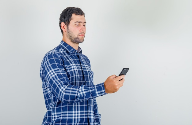 Young man using smartphone in checked shirt and looking careful. Free Photo