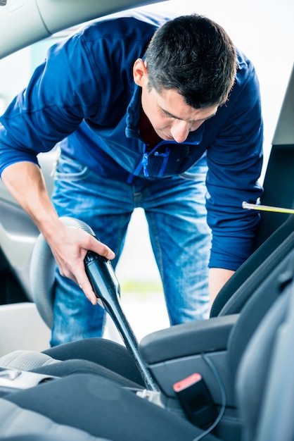 Young man using vacuum for cleaning the interior of a car Premium Photo