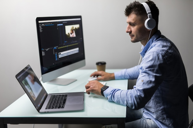Young man video editor with works with footage on his personal computer with big display in modern office Premium Photo