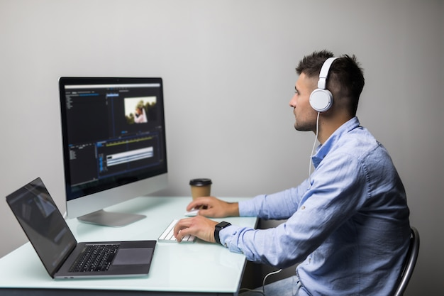 Young man videographer edits and cuts footage and sound on his personal computer at his office Premium Photo