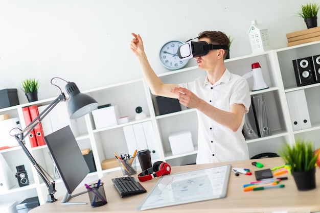 A young man in virtual reality glasses stands near the table and pulls his arm up. Premium Photo