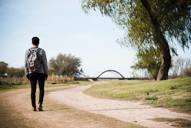 Young man walking into the park Free Photo