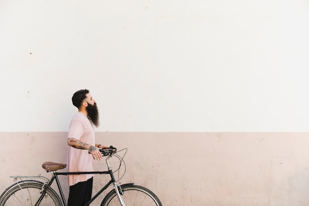 Young man walking with bicycle against painted wall Free Photo