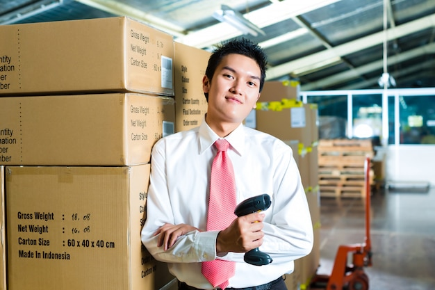 Young man in a warehouse with scanner Premium Photo