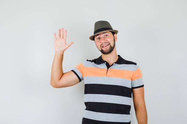 Giovane uomo agitando la mano per il saluto in t-shirt, cappello e guardando allegro. Foto Gratuite