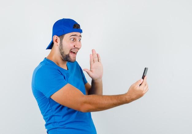 Молодой человек в синей футболке и кепке машет рукой в видеочате и выглядит веселым Бесплатные Фотографии