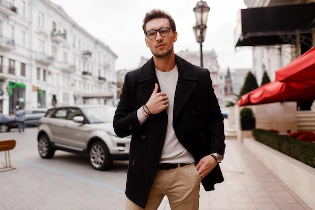 若い男が通りを歩いて秋の服を着ています。アーバンストリートでモダンなヘアスタイルを持つスタイリッシュな男。 無料写真
