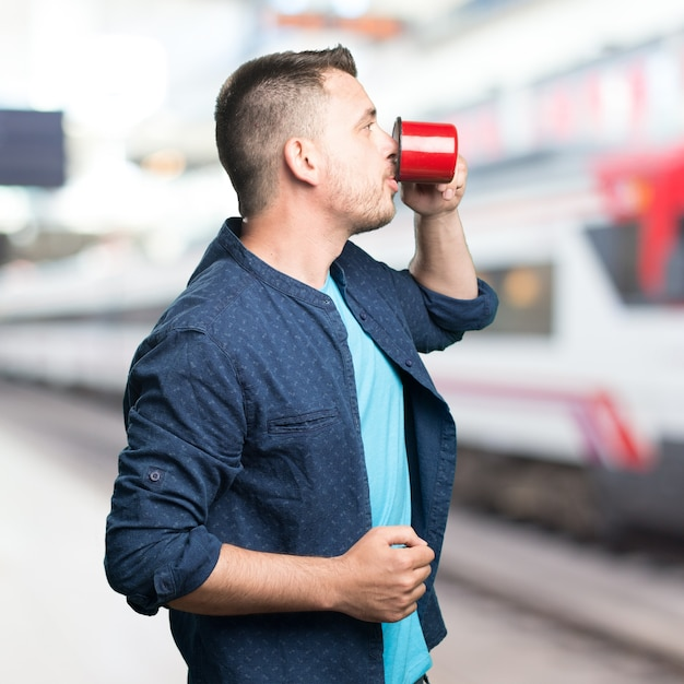 Young man wearing a blue outfit. holding a red cup. showing prof Free Photo