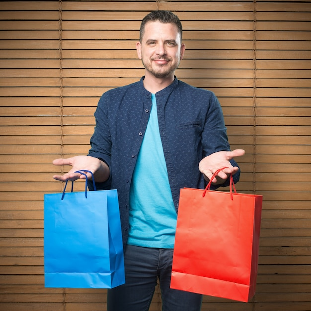 Young man wearing a blue outfit. holding shopping bags. Free Photo