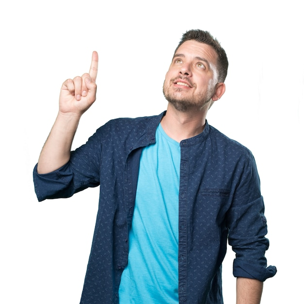 Young man wearing a blue outfit. pointing up with his finger. Free Photo