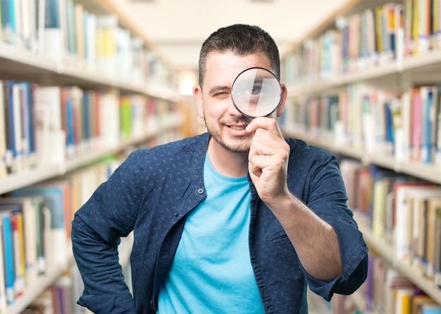 Young man wearing a blue outfit. using a magnifying glass. smili Free Photo