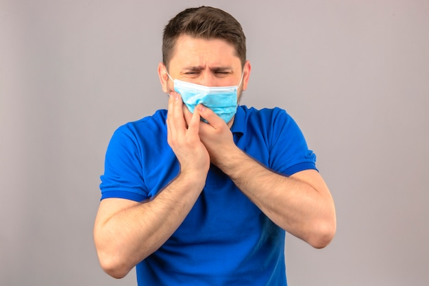 Young man wearing blue polo shirt in medical protective mask looking unwell touching cheek suffering from toothache over isolated white wall Free Photo