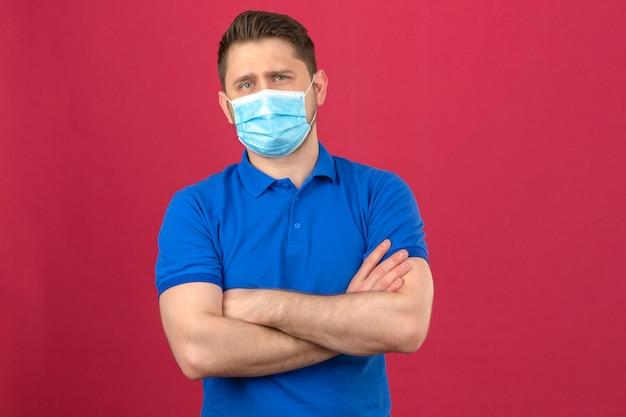Il giovane che porta la camicia di polo blu nella maschera protettiva medica che sta con le armi attraversate con sicuro esamina la parete rosa isolata Foto Gratuite