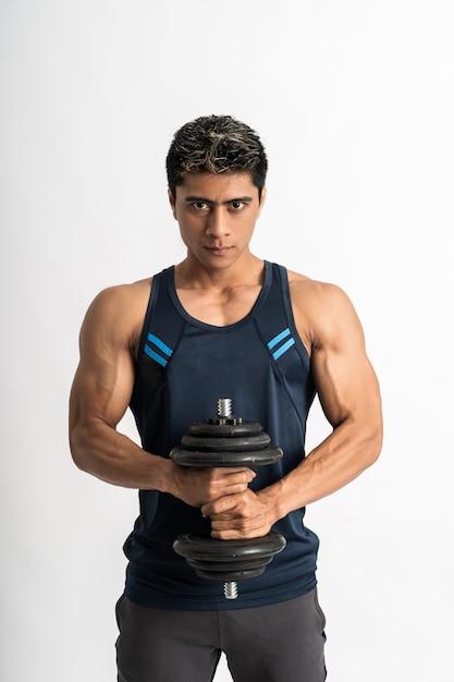 Молодой человек в спортивной одежде поднимает гантели обеими руками Premium Фотографии