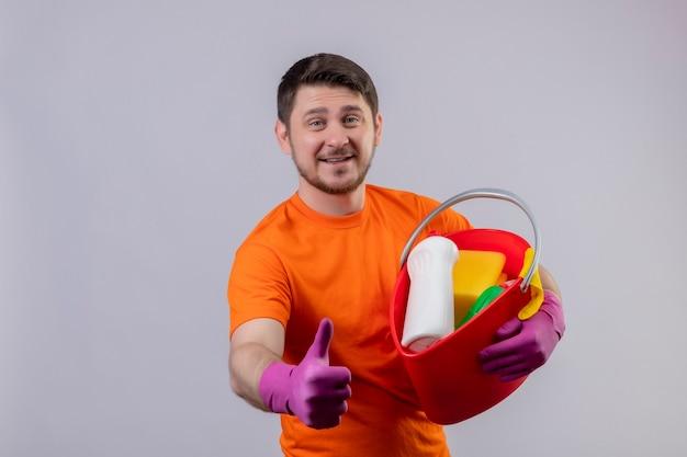 Молодой человек в оранжевой футболке и резиновых перчатках держит ведро с чистящими средствами Бесплатные Фотографии