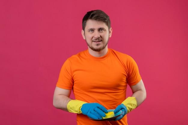 オレンジ色のtシャツとゴム手袋をはめてプレートとスポンジを保持しているピンクの壁に幸せと肯定的な立っている笑顔の若い男 無料写真