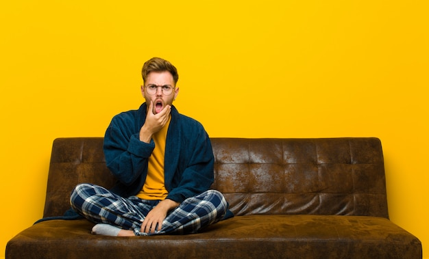 Young man wearing pajamas with mouth and eyes wide open and hand on chin, feeling unpleasantly shocked, saying what or wow . sitting on a sofa Premium Photo