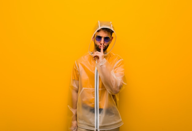 Young man wearing a rain coat keeping a secret or asking for silence Premium Photo