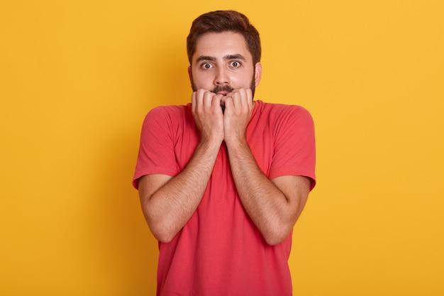 Молодой человек в красной майке стоит изолирован на желтом, парень выглядит испуганным, поразив выражение лица руками под подбородком, кусает палец, видит что-то ужасное. Бесплатные Фотографии