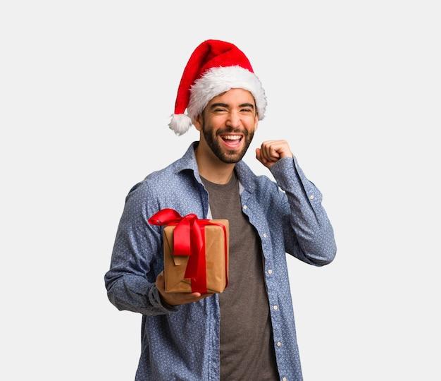 Young man wearing santa hat dancing and having fun Premium Photo
