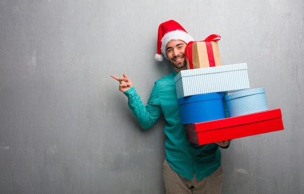 Young man wearing a santa hat holding gifts pointing to the side with finger Premium Photo