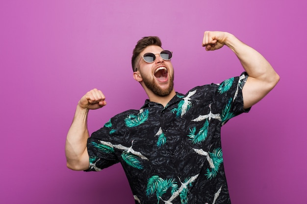 Young man wearing a vacation look raising fist after a victory, winner concept. Premium Photo
