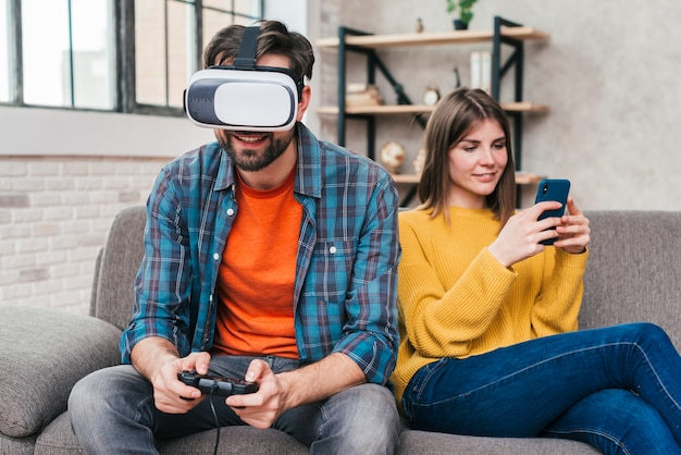 Young man wearing virtual reality glasses playing the video game with her wife using mobile phone Free Photo
