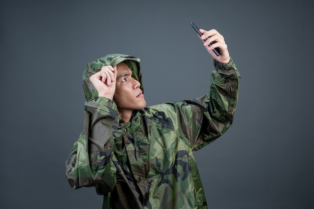 The young man wears a camouflage raincoat and shows different gestures. Free Photo