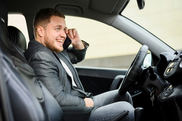 Young man at the wheel with his phone on his ear Free Photo