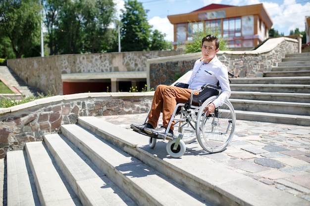 A young man in a wheelchair who can not descend the stairs. Premium Photo