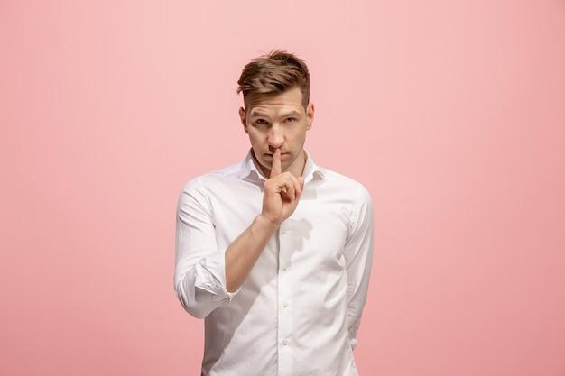 Il giovane sussurrando un segreto dietro la sua mano su sfondo rosa Foto Gratuite