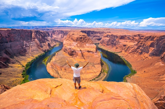 A young man in a white shirt and a green hat at horseshoe bend and the colorado river in the background, arizona. united states Premium Photo