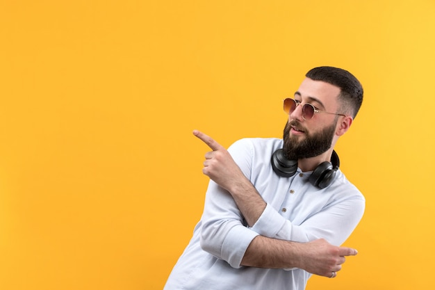 Young man in white shirt with beard, sunglasses and black headphones Free Photo