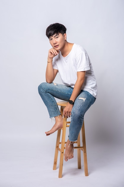 A young man in a white t-shirt is sitting on a high chair. Free Photo