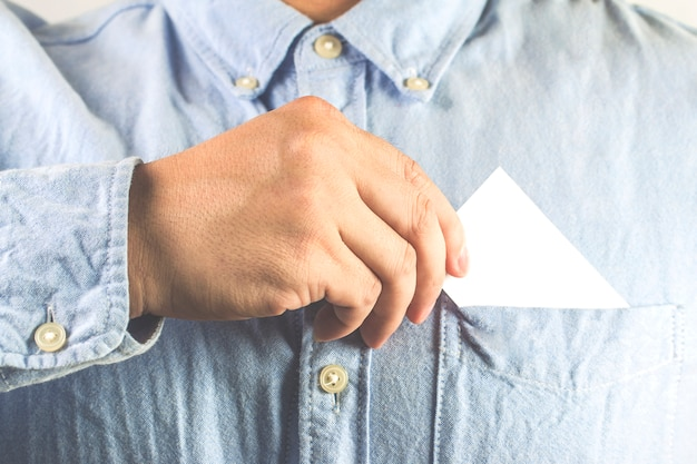 Young man who takes out blank business card from the pocket of his shirt Free Photo