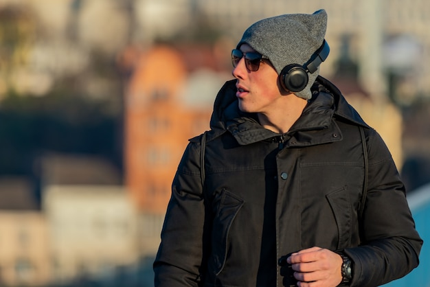 Young man in the winter city streets with headphones Premium Photo