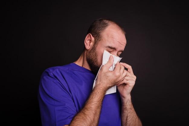Giovane che si pulisce il naso con un tovagliolo di carta su uno sfondo scuro -covid-19 Foto Gratuite