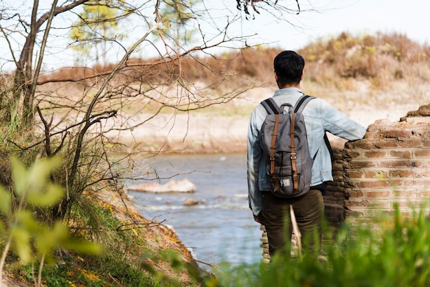 Young man with backpack looking at the lake Free Photo