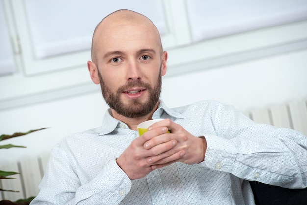 Young man with a beard drinking cup of coffee Premium Photo